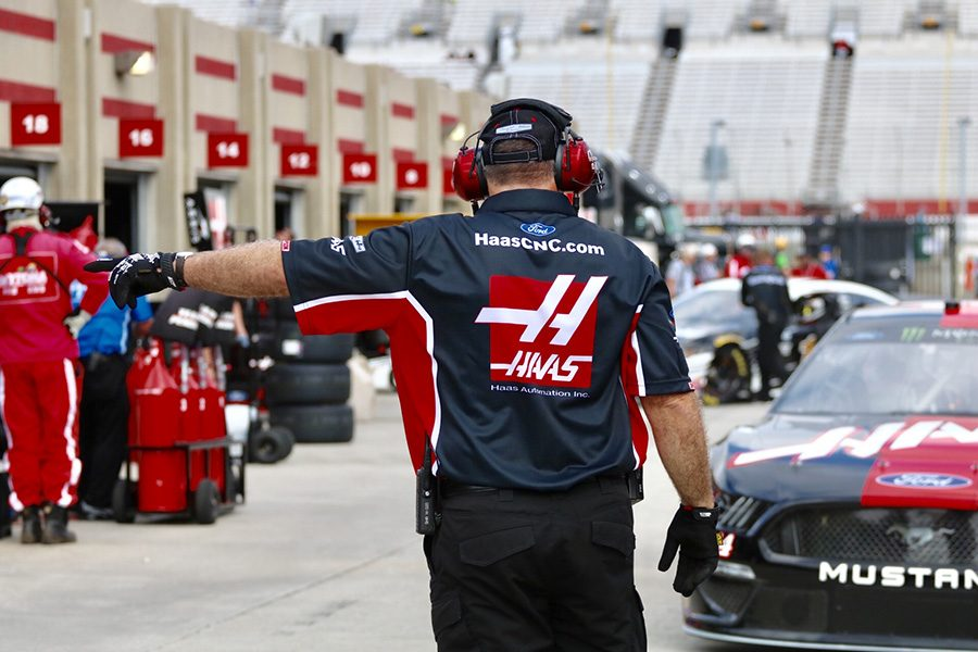 Pit+crew+member+of+the+No.+14+Haas+Automation+Ford+directs+Clint+Bowyer+into+his+designated+garage+during+the+first+Monster+Energy+NASCAR+Cup+Series+practice+of+the+day.+Bowyer+finished+practice+with+the+fastest+lap+time+of+30.774+seconds+at+a+top+speed+of+180.152+mph+after+only+running+six+laps.+%0A
