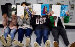 Several student's take a look at several different volumes of MUSINGS, the school's literary-art magazine. MUSINGS is currently accepting submissions for this year's magazine.