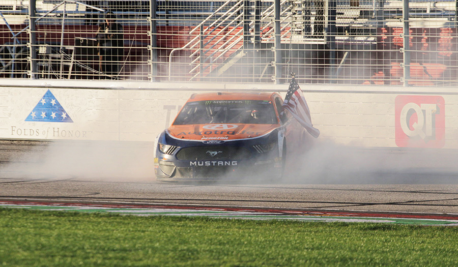 Brad Keselowski flies an American flag following his second career win in Atlanta. Keselowski spent most of the race shifting positions throughout the top-10, but his mistake-free driving allowed him to take the lead for the final 33 laps of the race.