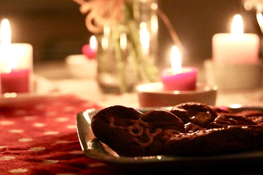 Feb. 14, 2019 - Valentine's day cookies lay on a table along with candles and flowers.