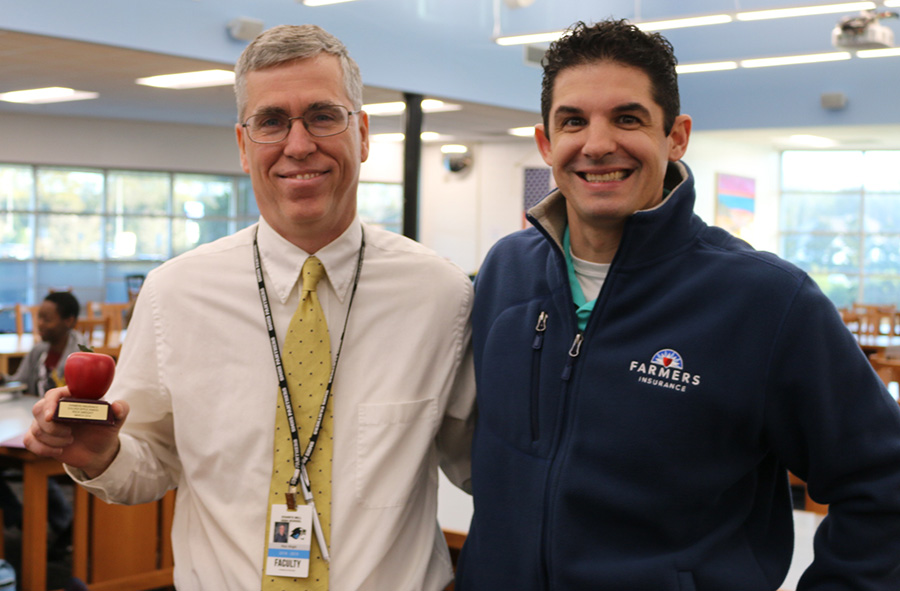 March's Golden Apple recipient, Rick Wright, poses with Tim Monihan from Farmers Insurance. One of the most important things to Wright is that the students at Starr's Mill have meaningful experiences during their high school careers.