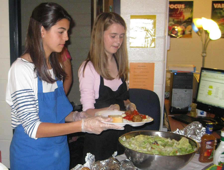 Family, Career and Community Leaders of America students serve pasta during the Mama Mia fundraiser. The dinner and themed basket silent auction will help purchase supplies for the Starr's Mill child development center.