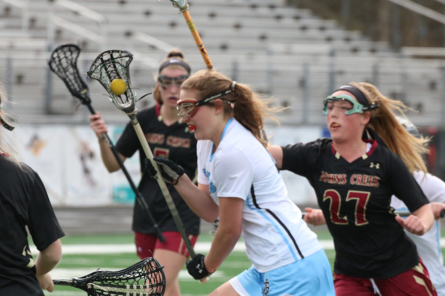 Junior Ryanne King sprints past Gladiator defenders. King did all she could for the Mill, scoring six of their nine goals. She has played a huge role in the offense's 102 goals scored this year.