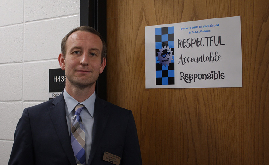 Assistant principal Scott Robinson pictured next to one of the PBIS (Positive Behavioral Interventions & Support) posters. For Starr's Mill, PBIS will really be about emphasizing what our school culture is and what values us panthers represent.