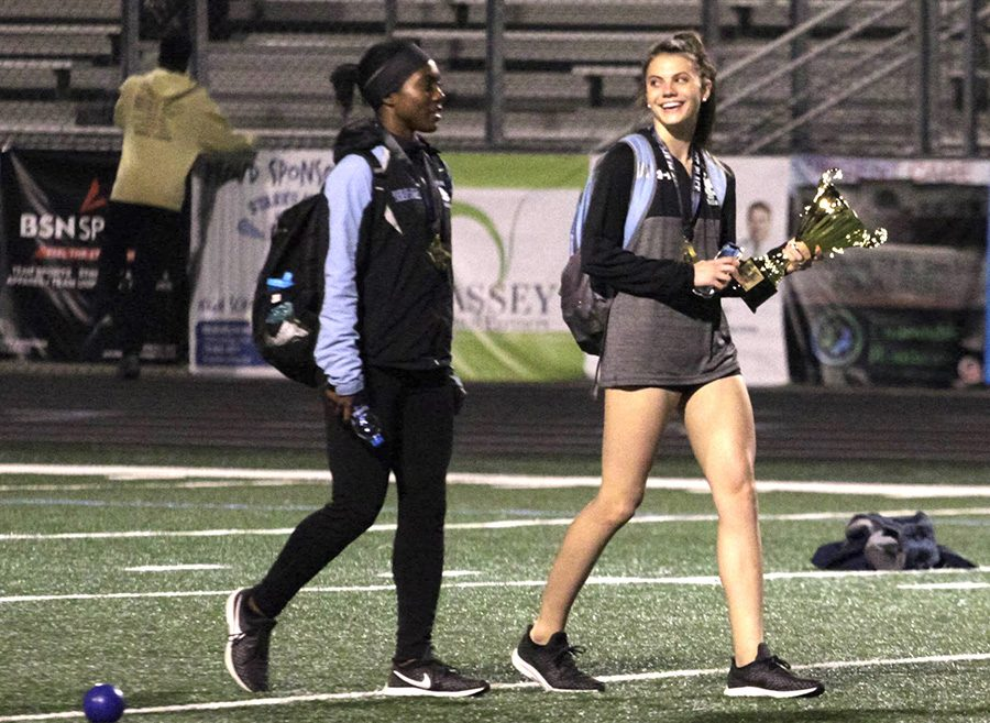 Senior Bree St. Julian and sophomore Allie Walker carry the first place trophy. Track and field competes again this weekend at the McEachern Invitational.