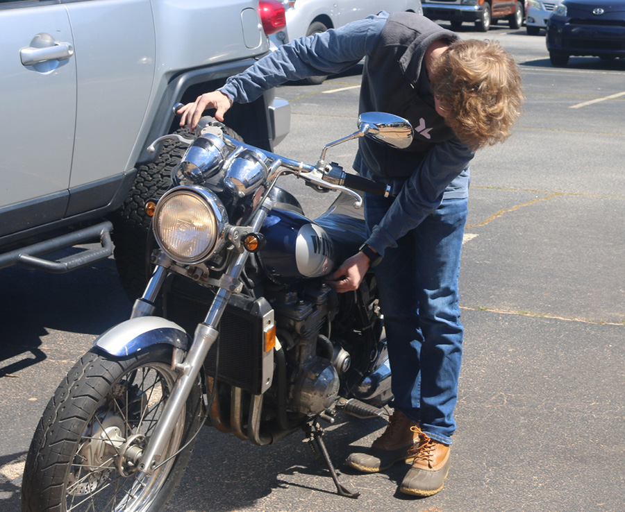 Junior Quinn Biddle starts up his motorcycle in front of his technology class. Biddle got a chance to drive his motorcycle to school so that he may show his accomplishment to the class.