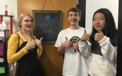 Eco Club members and juniors Brock Spence, Jackson Van Huffel, and Rebecca Tian celebrate Earth Day. The club is organizing a bingo game to promote environmental awareness.