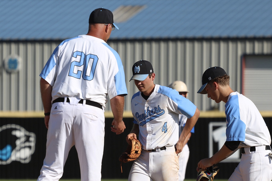 Head coach Brent Moseley talks with senior Brian Port and junior Beau Gardner at the mound during game three. In a series-determining game, the Panthers were unable to pick up the win, bringing an end to their season in the second round of the state playoffs despite winning a third straight region title.