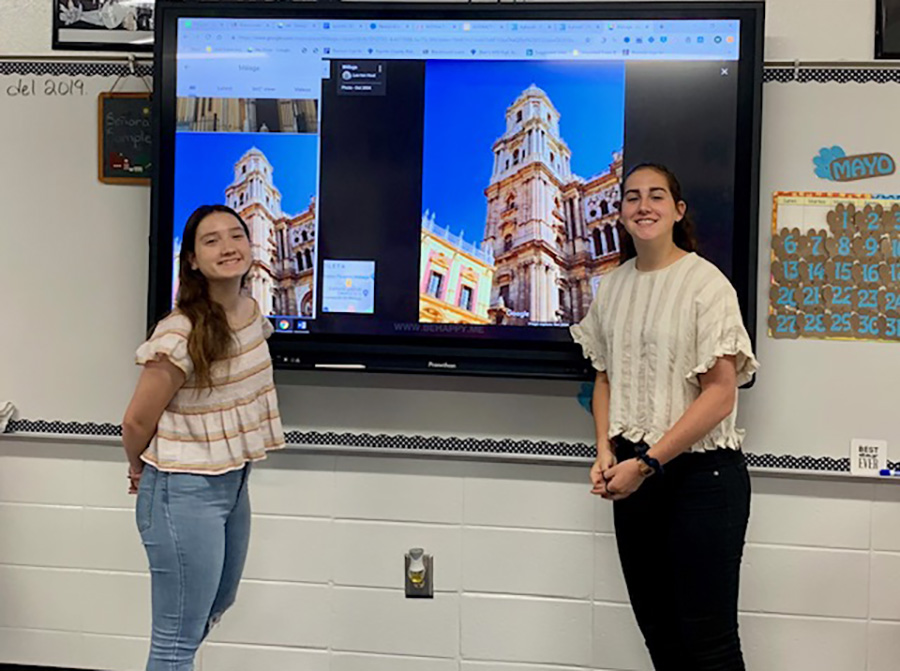 Foreign exchange students Marta Merida and Angela Valdo Perez stand with their presentation after the Interact Club meeting. The students made a presentation about their home country, Spain, and how the country compares to the United States.