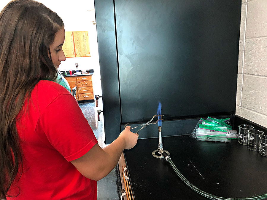 Aug.+28%2C+2019+-+Sophomore+Oreana+Bueno-Perez+burns+a+penny+on+a+Bunsen+burner+to+turn+it+into+fake+gold.+A+zinc+covered+penny+will+turn+a+golden+color+when+put+over+a+flame.