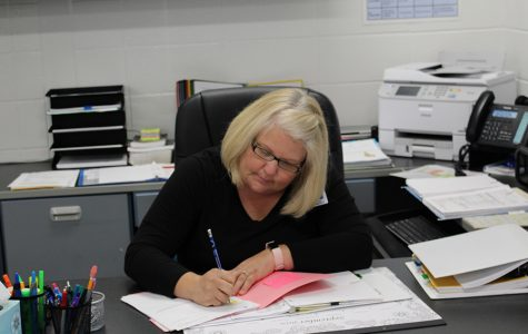 Athletic secretary Stacy Nichols completes paperwork at her desk. Nichols has worked as a secretary since 1994, and now moves from Oak Grove Elementary to the Mill.