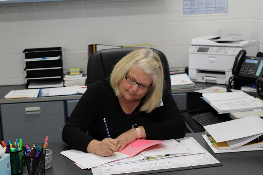 Athletic+secretary+Stacy+Nichols+completes+paperwork+at+her+desk.+Nichols+has+worked+as+a+secretary+since+1994%2C+and+now+moves+from+Oak+Grove+Elementary+to+the+Mill.
