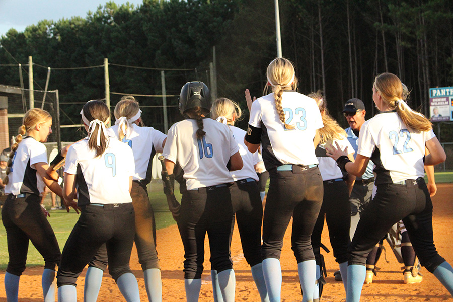 Softball team crowds at home plate to celebrate a home run by sophomore Sarah Latham. Starr's Mill hit three home runs during the series. The team had to come from behind in both games to sweep the Yellowjackets 10-7 and 10-5.