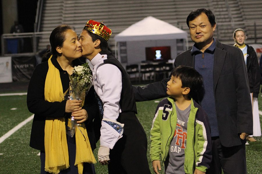 Senior+Jaeyoung+Choi+gives+his+mom+a+kiss+as+his+family+walks+onto+the+field.+Choi+showcased+his+talent+during+a+saxophone+solo+in+the+band%E2%80%99s+halftime+performance.