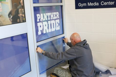 Dec. 11, 2019 - Maintenance worker places a blue cover onto the glass doors by the attendance office. These doors, along with the ones by the front office, are a new security addition to the school this year.