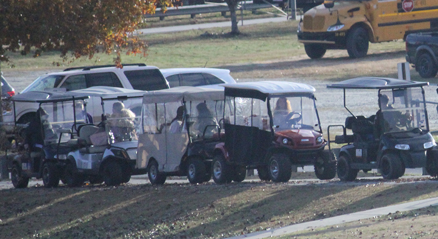 Golf+cart+drivers+look+back+in+line+as+they+leave+Starr%27s+Mill+to+see+one+cart+rear-ending+another.+The+frequent+accidents+involving+golf+carts+around+the+Mill+call+for+stricter+operating+regulations.