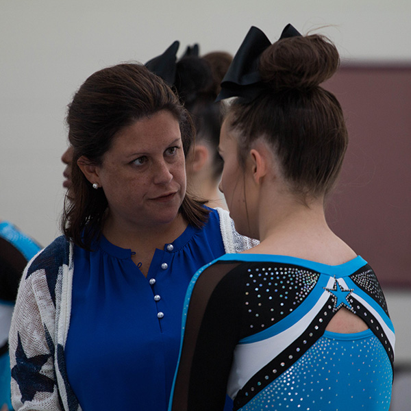 Competition cheer head coach Heather McNally instructs senior Hannah Defler before a competition in September 2018. McNally her resignation as the Starr's Mill head cheerleading coach in order to spend more time with her son.