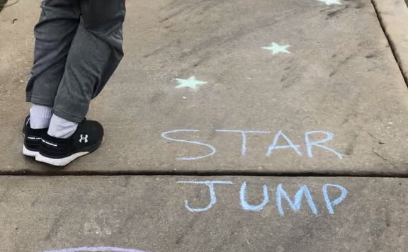 Angie Bryant's son participates in a chalk exercise for her workout video. Bryant sets up a routine and tries to have at least two days a week scheduled for physical activity.  Bryant's videos are just one example of how local community members are helping others during the coronavirus pandemic.