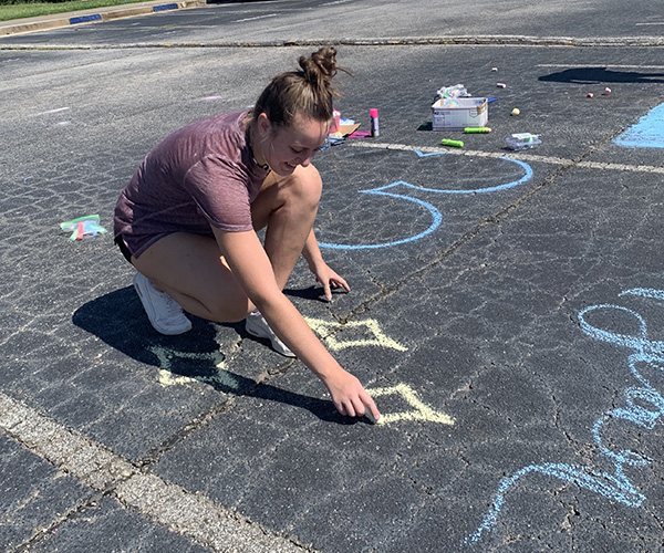 Senior Victoria Wiest decorates a parking spot with chalk on the Sunday before the first day of school. This day marks the beginning of the class of 2021's last year at Starr's Mill.