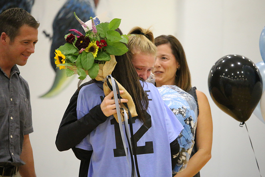 """Senior Ashlyn Mercure hugs her sister, sophomore Elise Mercure, during the senior night ceremony. """"It's sad [that it's my last year], but I'm glad I got to spend the last four years with this team,"""" Ashlyn said."""