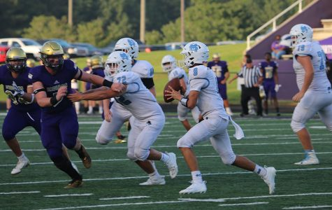 Sophomore Will Yarbrough scans the field for an open receiver during the Panthers' game against the East Coweta Indians in Sharpsburg last Thursday. A brand new Panther offense rose up, showing tons of promise in a tight contest that ended in a 21-20 victory for East Coweta. Yarbrough made his first start as the team's quarterback count with six pass completions for 127 yards and two touchdown passes as well as 11 carries for 25 yards. On the contrary, he still showed signs of inexperience with two lost fumbles in the second half.