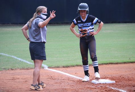 Coach Peyton Dean signals across the field as senior Lauren Flanders waits on the third base. This is Dean's first year at Starr's Mill High School after teaching at Rising Starr Middle School. She graduated from Armstrong State University, where she majored in health and physical science.
