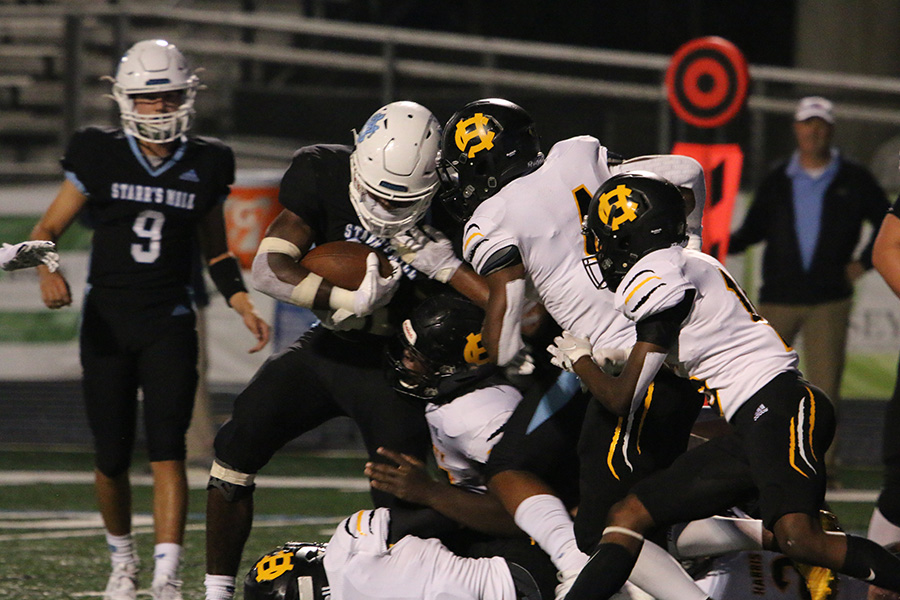 Sophomore running back Greigh Joseph fights through a Harris County defender during the Panthers' first region game against the Harris County Tigers. In a momentum-deciding game, Starr's Mill edged out Harris County 14-10 to start region play 1-0. Joseph had his first breakout game of the year with 13 carries for 60 yards and two touchdowns. Eight different rushers carried the ball for the Panthers, combining for 50 rushes that racked up 211 yards, one lost fumble, and 25:39 of game time.