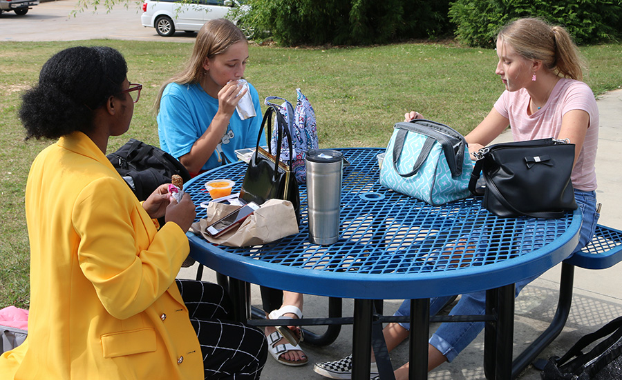 "Sophomores Ivey Breinig, Mia Haefner, and Alaina Campbell (left to right) eat lunch on the patio outside of the cafeteria. Students and faculty have been making adjustments in preparation for switching from the ""yellow"" hybrid A/B schedule to ""green"" merged schedule. The change takes effect Oct. 19 and includes switching from three to four lunch periods."