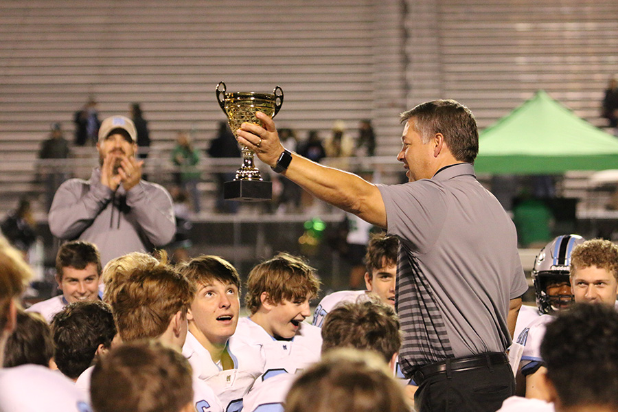 Head coach Chad Phillips hoists the region 2-AAAAA trophy in front of the football team after their victory against the McIntosh Chiefs last Friday. The Panthers took care of business to demolish the Chiefs 38-7. With this win, Starr's Mill clinched its fifth region championship in a row. This is also their ninth region championship in program history, breaking the county record previously owned by Sandy Creek with eight.