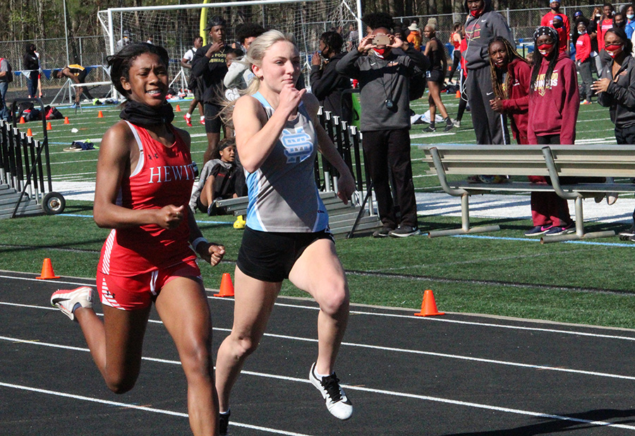 "Junior sprinter Sydney Blair keeps up with a runner from Hewitt-Trussville High School in Alabama during the annual Friday Night Lights meet. 18 boys teams and 21 girls teams gathered at Panther Stadium last Friday. Both boys and girls teams overall placed outside the top six. ""It was great competition tonight,"" track head coach Chad Walker said. ""It was a lot of fun, a little bit chilly, but we're going to build on this."""