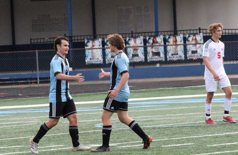 Senior defender Connor Marke (7) congratulates senior captain Brookly Muccillo (9) after a goal. Muccillo had two goals and two assists in the team's 10-0 win against Northside Columbus. The varsity girls defeated the Patriots 4-1 courtesy of senior Chloe Thompson's hat trick.