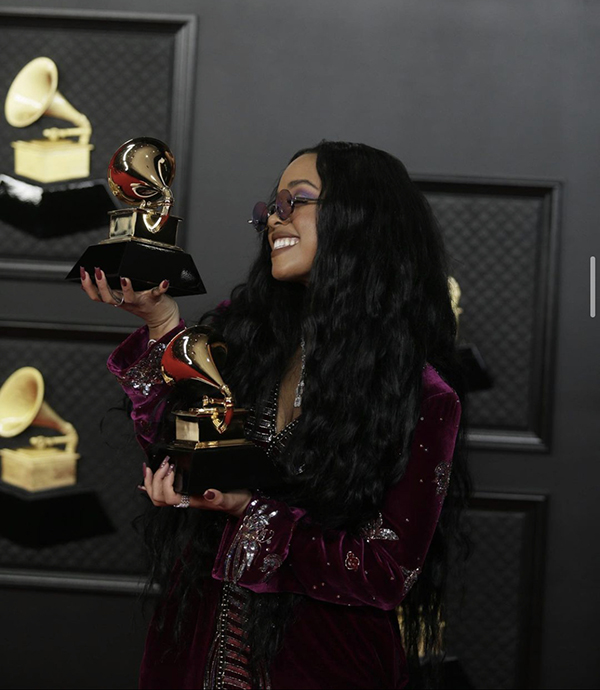 H.E.R. holds her Grammys for Song of the Year and R&B Song of the Year. Along with H.E.R., Taylor Swift and Beyonce made history at the 2021 Grammys. Swift became the first female to win three Album of the Year awards, and Beyonce became the winner of the most Grammys ever for a female artist.