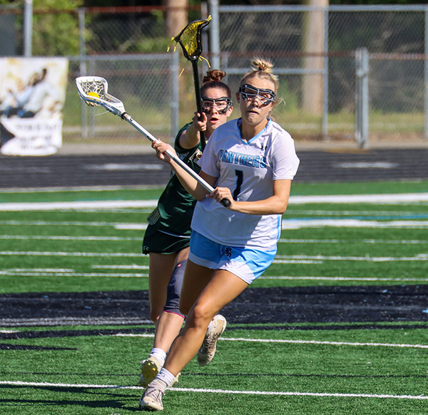 Junior Emma Grace Hepler scans the field, running past Wesleyan defenders in the GHSA quarterfinals. Hepler scored three goals, and assisted four more.