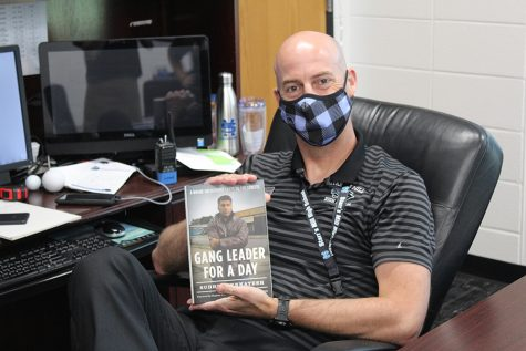 """Principal Allen Leonard sits at his desk with """"Gang Leader for a Day"""" by Sudhir Venkatesh. The book goes through a sociological study focused on the function of Chicago street gangs within the urban poor societies."""