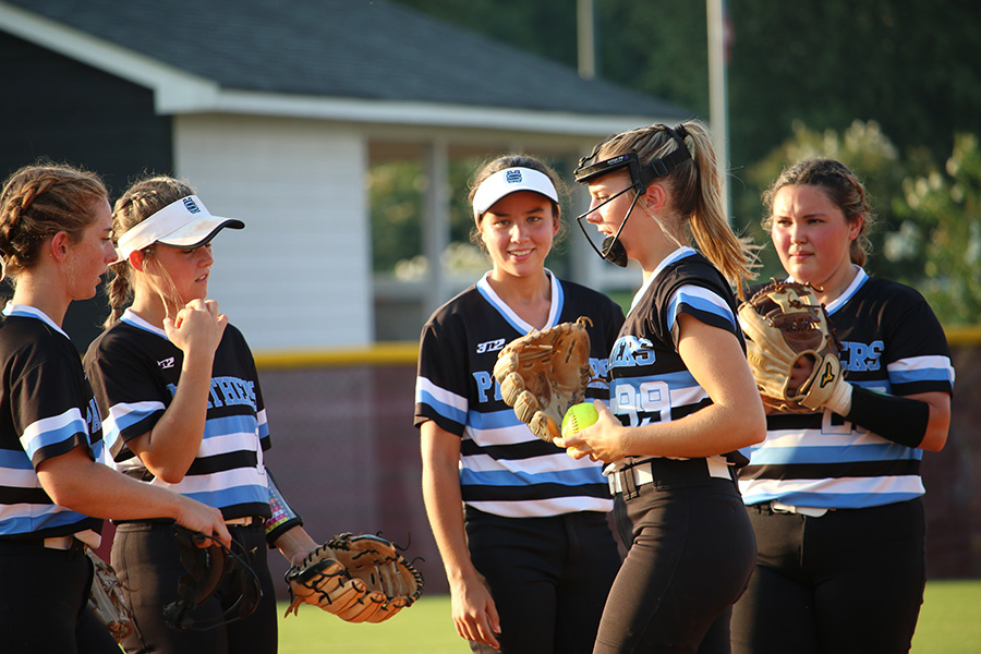 Lady Panthers gather to talk to senior pitcher Lili Backes (99) before a pitch. In a 6-1 loss, Backes gave up six runs on nine hits with eight strikeouts total.