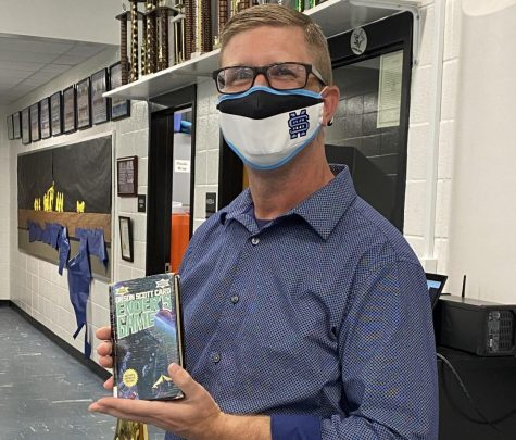 """Assistant band director Bert Groover holds his favorite book """"Ender's Game."""" He enjoys reading about the characters and the storyline that takes place in outer space."""
